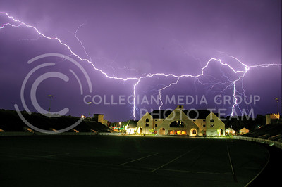 Lighting strikes, illuminating the sky behind Memorial Stadium   in a shade of striking violet during a fall storm.