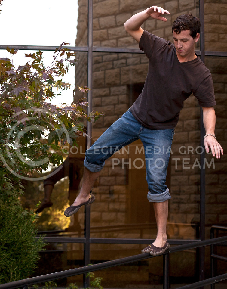 Jack Sparks, a senior in geography, balances himself on one foot on a rail behind Kedzie Hall Wednesday equipped with the vibrum show which Jack claims has developed his balance because of the shows structural design that  distributes weight in the same manner as bare feet.
