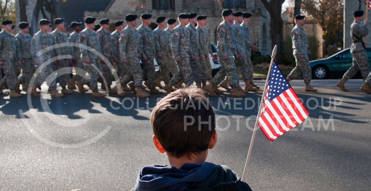 Nico Jimenez, Ft. Riley resident, waves a flag as troops from the 1st Infantry Division march past during the Veterans Day parade on Poyntz Avenue Thursday morning. Veterans Day was originally celebrated as Armistice day until 1954 when Congress changed the name.