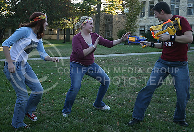 Sara Lynbe (left), junior in family studies and human services, and Jema Dubte (center), junior in anthropolpgy, attempt to turn Jesse Rigges (right), junior in journalism, into a zombie as he deffends himself armed with a nerf gun during their game of zombies verses humans in the quad wednesday afternoon.