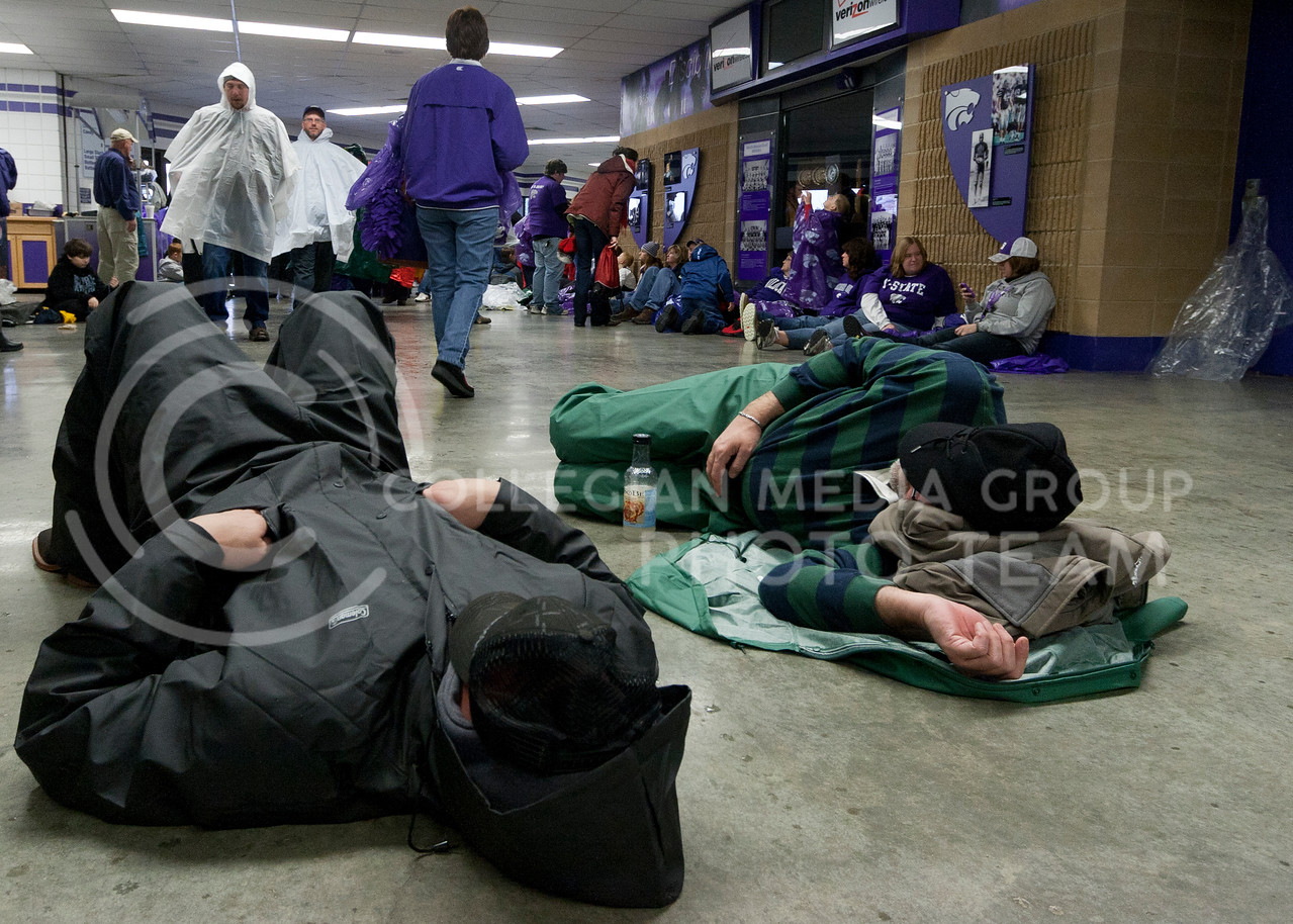 Fans take a nap in Bramlage Coliseum during the rain delay before Saturday's football game against Iowa State. The Cats won 30-23.