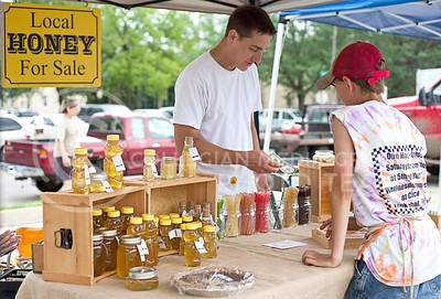 Clint Hibbs, Manhattan resident, sells his Simply Natural Honey during last year's farmer's  market on July 5.