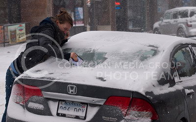 Mary Hineman, Manhattan resident, cleans off the ice on her back window in Aggieville on Tuesday afternoon.