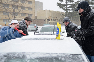 (Left to right) Luke Werhan, freshman in communication studies, Tyre Kartley, senior in secondary education, Conor Milne, sophomore in psychology, and Wes Gardner sophomore in agricultural economics help a female Haymaker freshman by clearing her car of ice and snow so she could go to the hospital Tuesday afternoon outside Haymaker Hall.