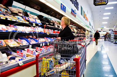 Judy Zerr, Manhattan resident, looks through refrigerated food while grocery shopping at Ray's Apple Market Tuesday morning.