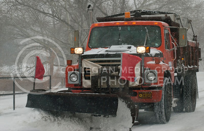 Snow plows work Tuesday afternoon to clear off roads on campus and around Manhattan as snow continued to fall.