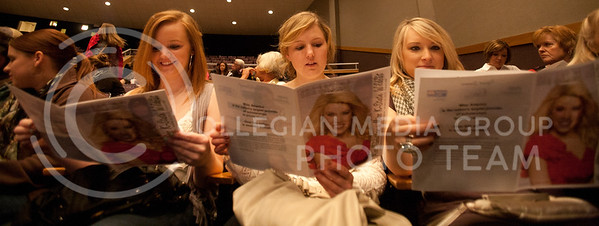Supporters of Miss K-State participant Kristin Blecha, Dana Drake, senior in family studies, Elle Stoss, senior in accounting, and Joanna Brown, Manhattan citizen, look through the program on Sunday afternoon. The pagent was held in Forum Hall at 2 p.m. Sunday.