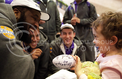 Ralph Guidry, left, a member of the K-State football team, shares a laugh with Kate, a 4-year-old patient at the Texas Scottish Rite Hospital for children, Thursday morning. The entire football team visited the hospital to sign autographs and mingle with the children.