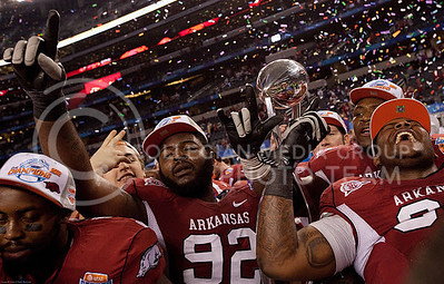 After defeating K-State in the 2012 Cotton Bowl, members of the Arkansas football team celebrate as confetti flies in Cowboys Stadium.