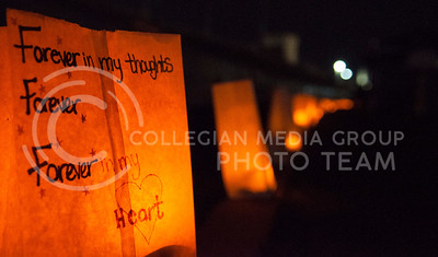 (Photo by Hannah Hunsinger | Collegian)  Paper bags, weighed down by donated cans of food and illuminated by LED candles bearing messages written to loved ones lost to cancer line the track at Memorial Stadium during the K-State Relay for Life on Friday, April 12, 2013.