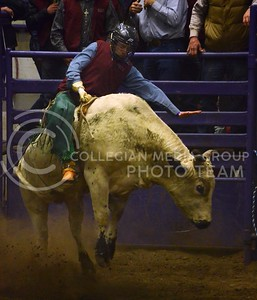 (Photo by Parker Robb | Collegian)  A bull rider from Fort Scott Community College holds on for dear life as the bull dashes from the starting gate with him on its back during the bull riding competition at the first day of the annual K-State Rodeo February 22 at Weber Arena.
