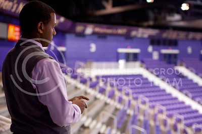 After the crowds had dispersed from their seats at Bramlage Coliseum, Adrian Esquilin waits on head coach Bruce Weber to finish up an interview on the court before releasing his green shirt staff. Once staff is released, they report to the main office to sign out and have brief meetings before calling it a night.  (Photo by Evert Nelson | Collegian)