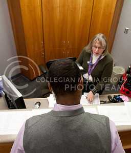 Adrian Esquilin looks over shift schedules with Kathy in the main office in Bramlege Coliseum during the Wildcats game against Texas Tech.  (Photo by Evert Nelson | Collegian)
