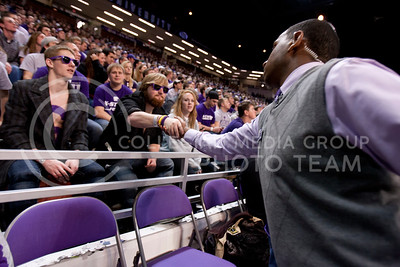 While making his rounds, Adrian Esquilin reaches out to shake the hand of Nolan Regnier, sophomore in secondary education, before the begining of the Wildcat's game against Texas Tech in Bramlege Coliseum.  (Photo by Evert Nelson | Collegian)