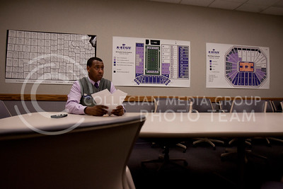 Sitting in a meeting room adjacent to the main office at Bramlage Coliseum, Adrian Esquilin takes a moment to stare into space before going back to organizing schedules for an upcoming high school basketball tournament being hosted at Bramlage.  (Photo by Evert Nelson | Collegian)