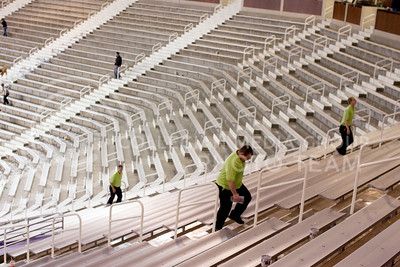 Staff workers make their way up bleachers at Bramlage Coliseum after the Texas Tech game.  (Photo by Evert Nelson | Collegian)