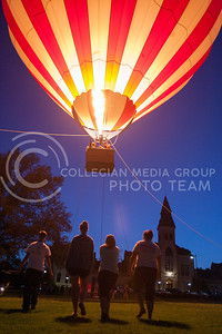 Students helping guide a hot air balloon to a safe landing walk towards the glowing orb in front of Anderson Hall Monday night. Rides on the balloon were offered as the event was put on by UPC.  (Photo by Evert Nelson | Collegian)