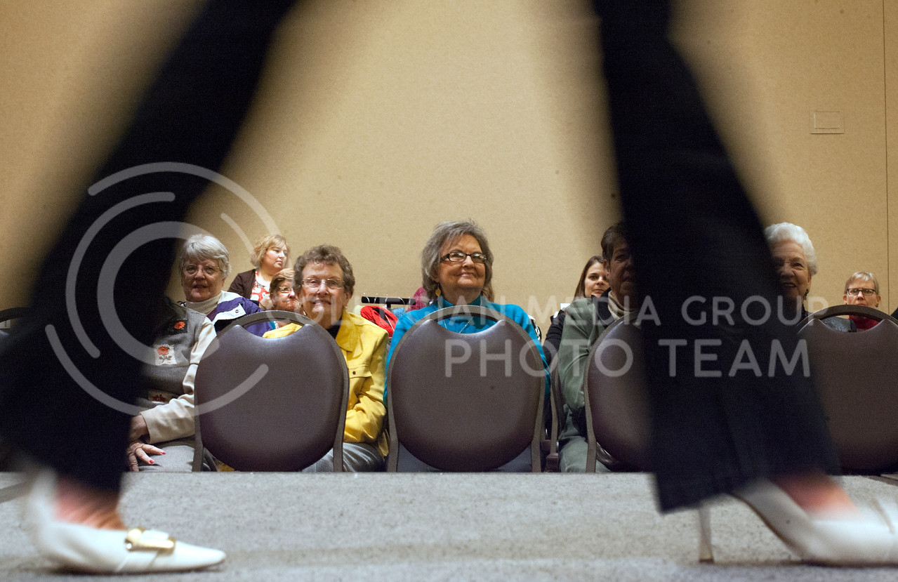 Women sit across from a runway to watch a fashion show at the Festival of Trees event Monday night at the Alumni Center.