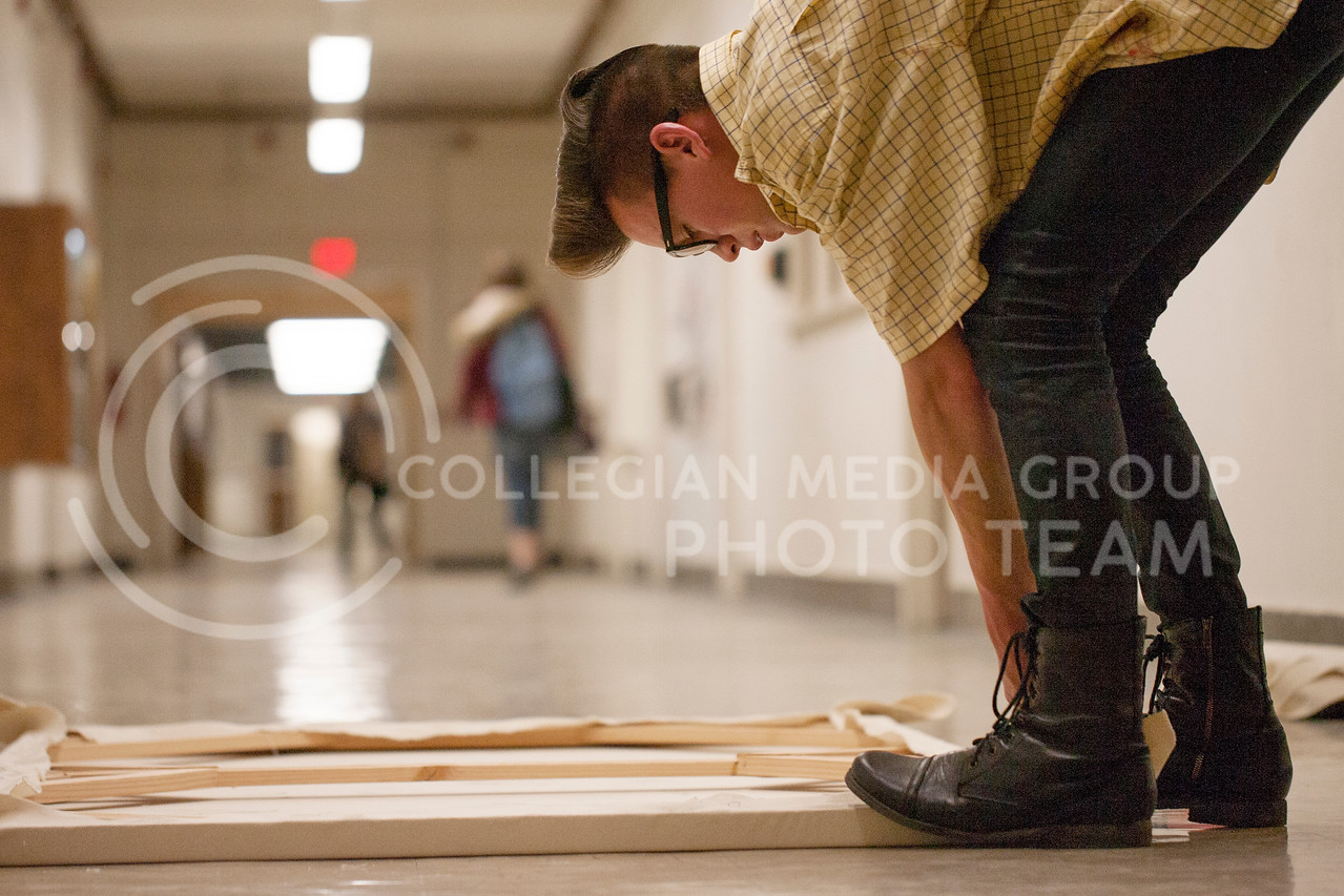 Working to stretch canvas for a painting, Hunter Scott, non-degree seeking grad student, uses the hallway of Willard Hall Tuesday night as his work area.<br /> <br /> (Photo by Evert Nelson | Collegian)