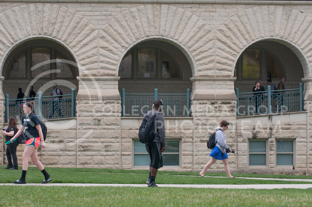 Students walk on the crossing sidewalks in front of Hale Library Tuesday morning on their way to and from classes. After a warm morning Tuesday was followed by a cold and rainy afternoon to delay the spring weather once again.<br /> <br /> (Photo by Evert Nelson | Collegian)