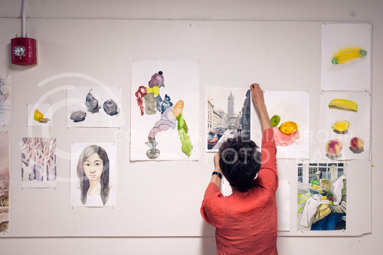 Nancy Moorow, painting and drawing instructor, pins up her Water Media 1 students works of art in the second story of Willard Hall Thursday night. The medium uses water mixed with trasparent watercolor, acrylic, and ink.<br /> <br /> (Photo by Evert Nelson | Collegian)