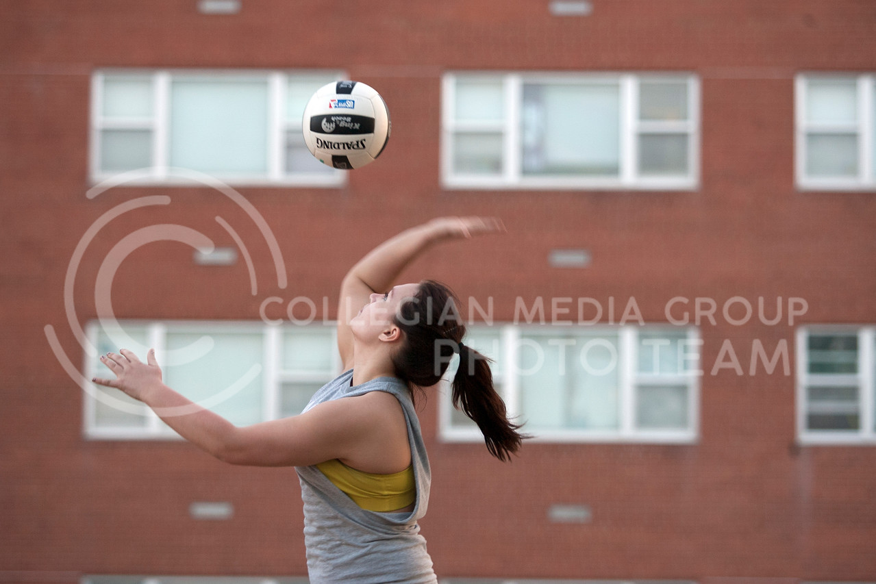 Melissa Evans, freshman studying microbiology and pre nursing, serves a volleyball in front of Goodnow Hall Tuesday evening. The warm weather brought many students and residents around Manhattan outside.<br /> <br /> (Photo by Evert Nelson | Collegian)