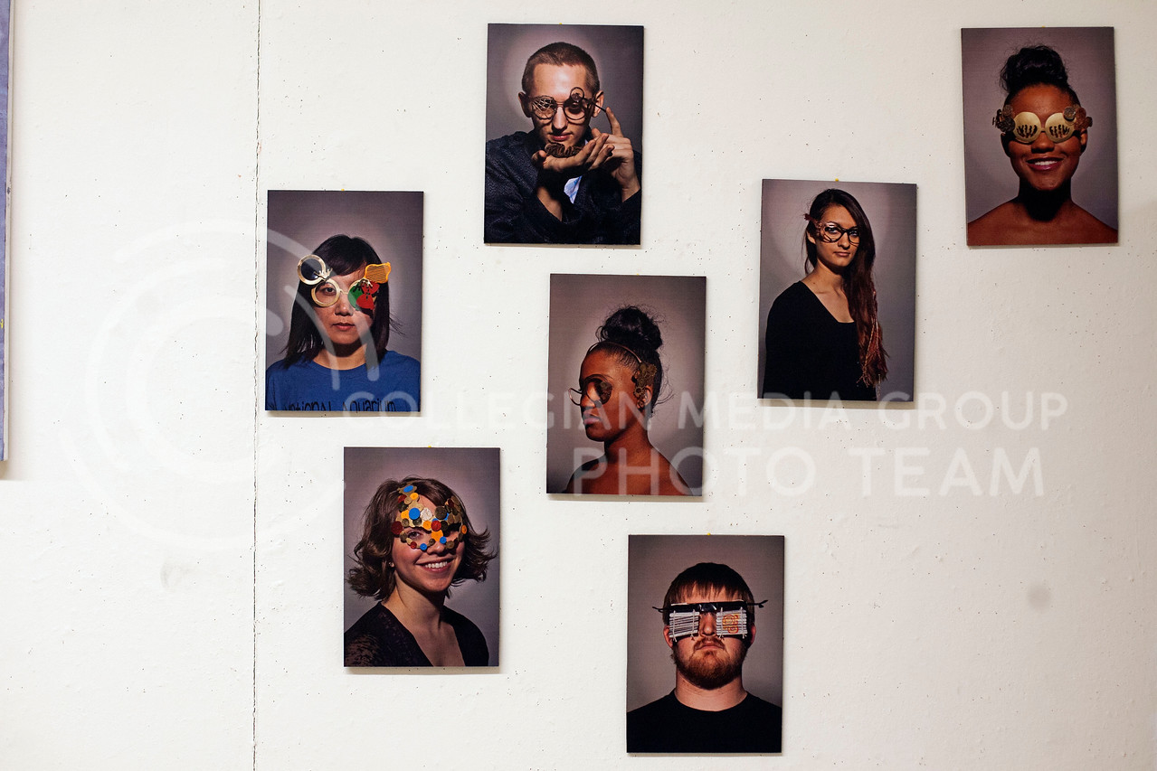 Photographes of students with different props take up room on the third story wall of Willard Hall Thursday night.<br /> <br /> (Photo by Evert Nelson | Collegian)
