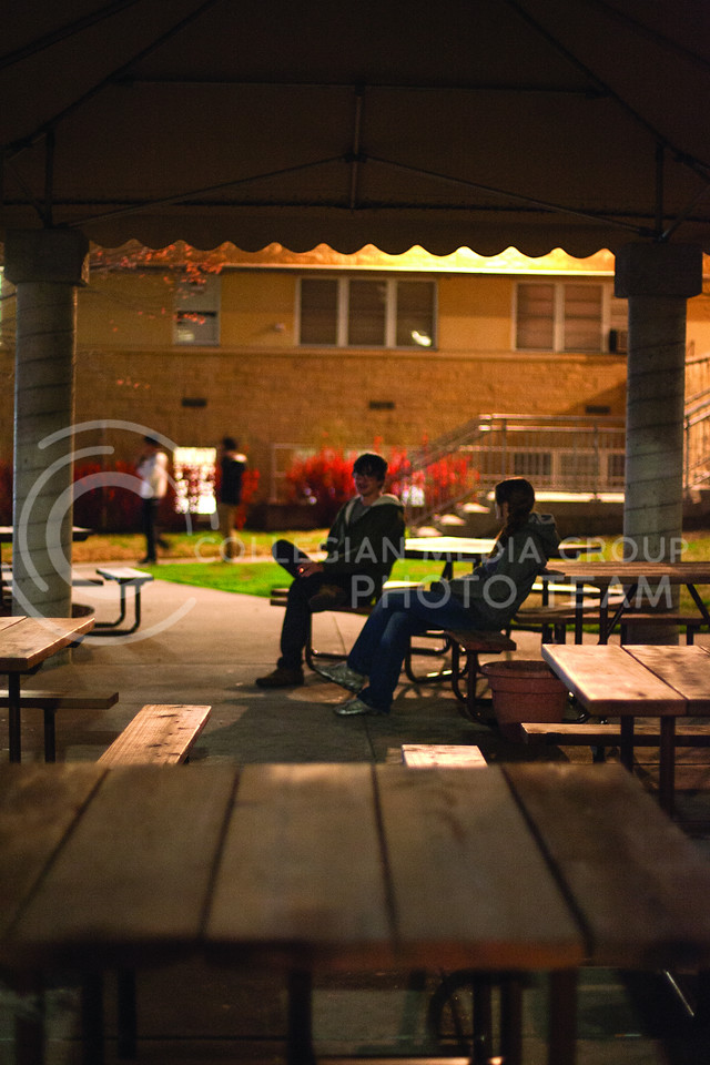 Stephanie Matis (left), junior studying eearly education, and Oliver Henry (right), freshman studying microbiology, sit at pinic tables under a canepy outside of Derby Dining Center Monday night as other students walk out of Moore Hall.<br /> <br /> (Photo by Evert Nelson | Collegian)