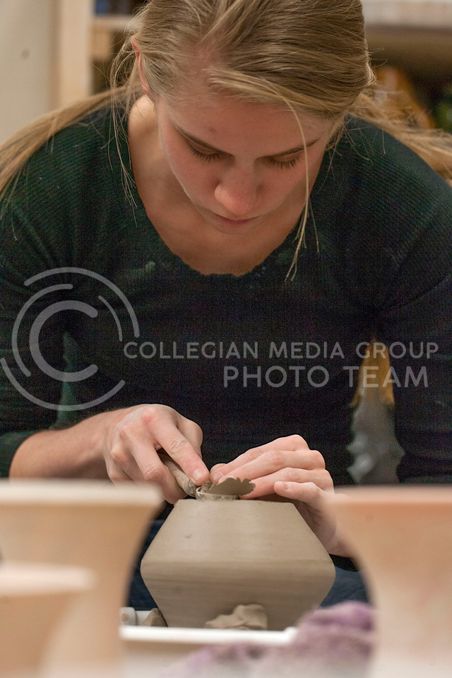 "Kelli Janzen, junionr in graphic design, works on scupting a piece of clay for her ceramics 1 class Thursday night in Willard Hall. ""For me it's getting the weight at the bottom,"" Janzen said talking about her work on a bottle. <br /> <br /> (Photo by Evert Nelson 