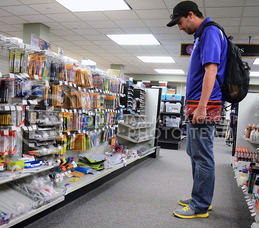 (Photo by Parker Robb | Collegian)  Andrew McNeive, senior in horticulture and landscape design, shops for pens among the many pen designs for sale in the Union Bookstore in the K-State Student Union Wednesday afternoon.