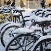 (Photo by Parker Robb | Collegian)<br /> <br /> K-State students trudge past bicycles covered in snow in Bosco Student Plaza the morning of January 30. Just a day and a half after setting a record high temperature for January 28th, Manhattan received three inches of snow.