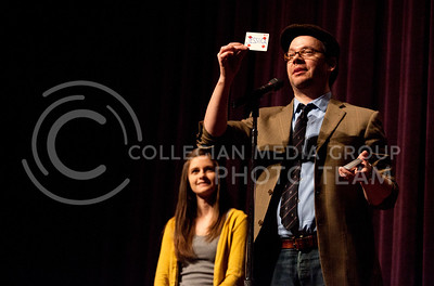 "A four of diamonds with ""Jessica"" is held up to the crowd by comic magician Derek Hughes (right) Saturday during his show in Forum Hall. Jessica Synons (left), fifth year architecture student, was chosen to come up on stage to help with one of the tricks.  (Photo by Evert Nelson / Collegian)"
