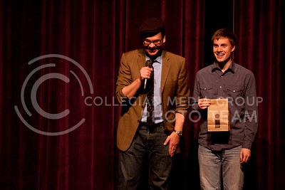 """Derek Hughes (left) laughs next to his audience helper Jordan Crook (right), junior studying architecture, during a trick where Hughes uses two bags representing """"reality"""" and """"imaginary"""" worlds. Hughes comedy magic show, hosted by UPC, was held in Forum Hall Saturday night.  (Photo by Evert Nelson / Collegian)"""