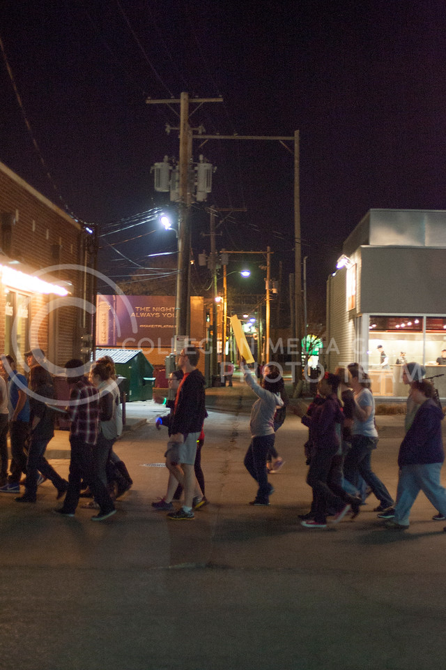Supporters for Take The Night, an event against women violence, march through Aggieville Thursday night chanting to gain more support.<br /> <br /> (Photo by Evert Nelson | Collegian)