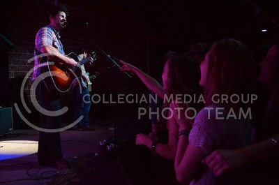 (Photo by Parker Robb | Collegian)  Students in the very front row cheer as JT Hodges sings one of his well known country songs during his performance at Aggieville Central Station May 4, 2013.