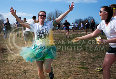 (Photo by Hannah Hunsinger | Collegian)   A participant gets in the Powercat Paint Run 5K gets yellow paint powder thrown at her as she runs.  The event, which took place at at Warner Memorial Park on Saturday, April 6, 2013 was hosted by men and women of Alpha Tau Omega and Alpha Delta Pi and benefited the Ronald McDonald House Charities,