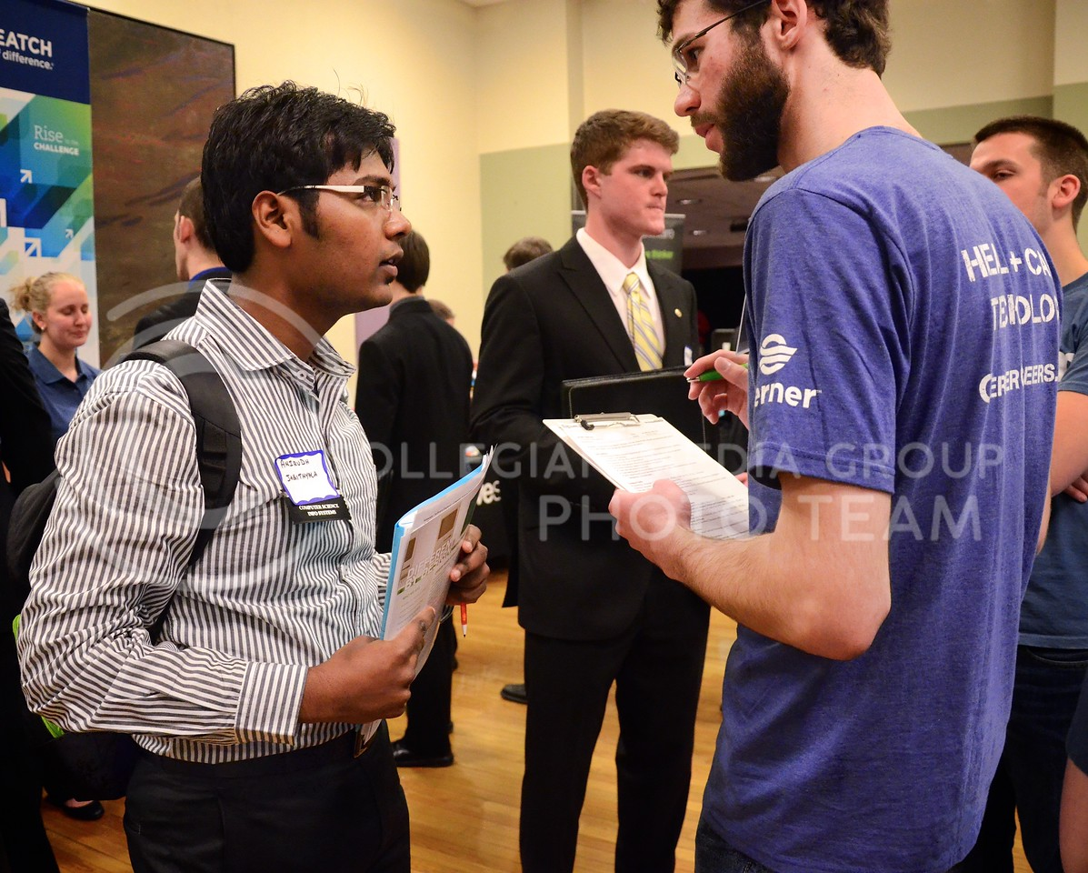 (Photo by Parker Robb | Collegian)<br /> <br /> Anirudh Jagithyala, graduate student in computer science, discusses internship and job opportunities with Eric Riley, a recruiter for Cerner Corporation, at the Engineering Career Fair Tuesday afternoon at the K-State Student Union. Over 100 companies were present at the career fair Tuesday, and about 50 plan to set up shop Wednesday.