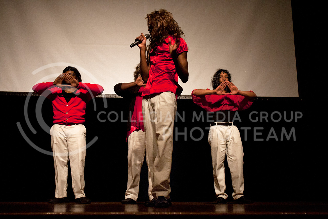 Sporting wigs, sweaters, and blouses, members of Alpha Phi Alpha interpret Delta Sigma Theta during their step routine Tuesday night. The Switch Day event was held in Fourm Hall in the student union.<br /> <br /> (Photo by Evert Nelson | Collegian)