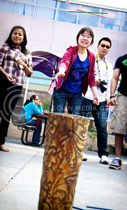 """(Photo by Jed Barker   Collegian) Sin Dee Tey, a junior in dietetics, plays a Chinese game called """"Tou Hu"""" in which players toss slender, colored sticks, trying to get as many into the can.  The game was part of the International Week Parade and Game Day on April 6, 2013."""