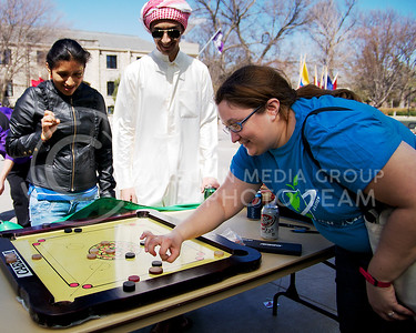 "(Photo by Jed Barker | Collegian) Elizabeth Cardy (right), a masters student in Theatre, and Rosa Tenelema (left), a teacher from Ecuador with the Go Teacher Program, play a game called ""kerim"" while Mazeen Alqaseer (center), a freshman in architectural engineering from Saudi Arabia, makes sure they play by the rules. ""Kerim"" is a middle eastern game that is similar to pool.  The players flick a wooden chip and try to hit other chips into the slots in the corners. The game was part of the International Week Parade and Game Day on April 6, 2013."
