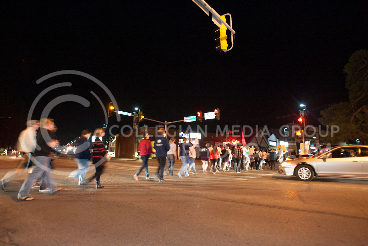 Marching across Anderson Avenue, people participating in Take Back The Night stop traffic while making their way around Aggieville Thursday night.<br /> <br /> (Photo by Evert Nelson | Collegian)