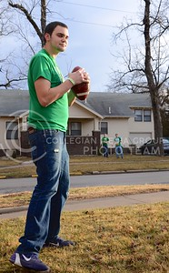 (Photo by Parker Robb | Collegian)  A Fake Patty's Day reveler passes a football back and forth with friends across the street March 9 at 16th and Laramie Streets.