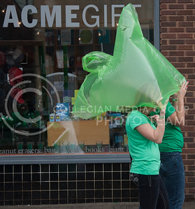 Hayley Lorenzini (left) senior studying kinesiology, uses a green pancho with Caroline Lynch (right), senior studying political science, to stay dry during the rain Saturday in Aggieville.  (Photo by Evert Nelson | Collegian)