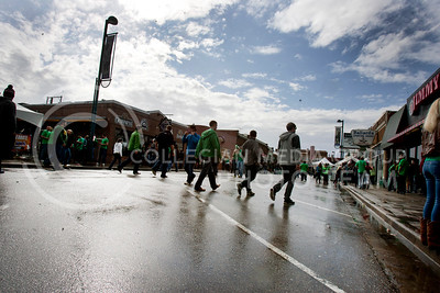 The sun comes out breifly to reflect light off a wet Moro Street Saturday as students and other people flocked to Aggieville to partake in Fake Patty's Day.  (Photo by Evert Nelson | Collegian)