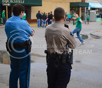 (Photo by Parker Robb | Collegian)  A Fake Patty's Day reveler drunkenly dances in front of law enforcement officers March 9 in Aggieville.