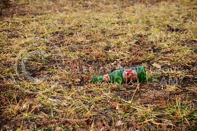 (Photo by Parker Robb | Collegian)  An empty bottle litters the grounds of Manhattan Christian College near Aggieville on Fake Patty's Day March 9.