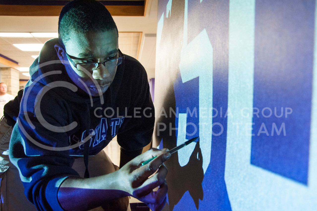 """(Photo by Hannah Hunsinger   Collegian)<br /> <br /> Because the first floor has the main lobby of West Hall, there is no colorful mural decoating one of its wall. So Hill took it upon himself to design and create a mural on canvas to hang in his lobby. On April 2, 2013, in the lobby of the first floor, Hill uses a projector to trace """"KSU"""" on the canvas, which will then be block out with newsaper and tape and painted over to create silver letters on a purple field."""
