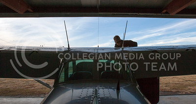 Ron Jones checks oil levels in a Cessna at Manhattan Regional Airport during his pre-flight routine.  (Photo by Evert Nelson/Collegian)