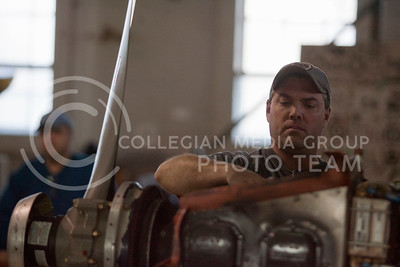 Bill Radenberg, Manhattan resident, working on a very expensive airplane engine in a stone hanger at Manhattan Municipal Airport. Randenberg is also a mechanic for the KSU flying club and works on repairs on the planes the club uses.  (Photo by Evert Nelson/Collegian)