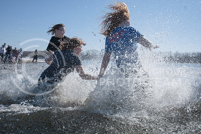 A group of girls fall into the icy lake water at Tuttle Creek swim beach Saturday for the Polar Plunge event.  (Photo by Evert Nelson/Collegian)